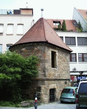 """Zwinger: Freier Raum zwischen der Hauptmauer und einer vorgelagerten Zwingermauer als Teil der mittelalterlichen Stadtbefestigung. Bei deren Abbruch ab 1818 blieben hier ein Stück Hauptmauer mit Wehrturm (""""Kesselturm"""") sowie ein Stück Zwingermauer samt Rundturm erhalten."""