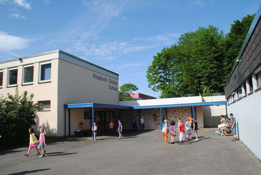 Schule_Pausenhof_mit_Boulderwand_und_Turnhalle