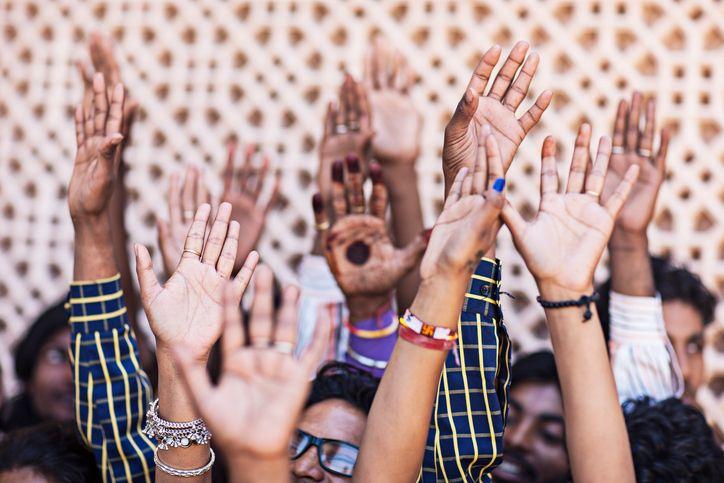 Bild: Menschen heben die Hände zur Wahl