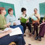 Sechs Frauen sitzen nebeneinander und lernen