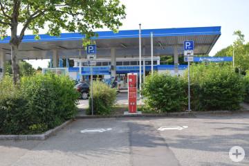 Das Bild zeigt eine Stromladesäule zwischen zwei öffentlichen Parkplätzen. Im Hintergrund ist eine Tankstelle zu sehen.