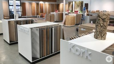 Das Bild zeigt ein Einrichtungsgeschäft, in dem verschiedene Bodenbelägen wie Kork und Laminat ausgestellt sind.