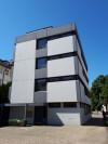 Das Bild zeigt ein vierstöckiges Gebäude mit Flachdach von der Seite.
