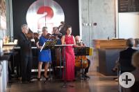 Zu sehen sind Streichmusiker und eine Sängerin bei einem Auftritt in der Tonne.