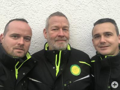 Zu sehen sind drei Männer, zwei jüngere und ein im Vergleich zu den beiden etwas älterer in der Mitte. Sie tragen schwarze Jacken mit neongelben Reißverschlüssen und schauen direkt in die Kamera.