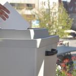 Hand die einen Umschlag in eine graue Wahlurne wirft