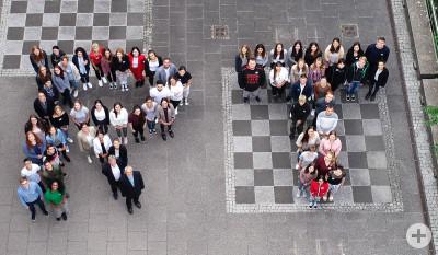 Gruppenfoto Azubis: Von oben fotografiert, bilden die jungen Menschen ein R und ein T.