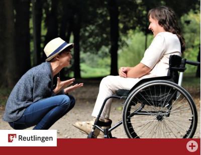 Zu sehen ist eine junge Frau im Rollstuhl, der ein junger Mann mit Hut gegenüberkniet und ihr lächelnd etwas zu erzählen scheint.