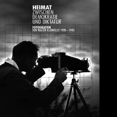 """Das in Graustufen gehaltene Bild zur Ausstellung """"Heimat zwischen Demokratie und Diktatur"""" von Walter Kleinfeldt zeigt einen Mann von der Seite, der durch eine antike Kamera schaut."""