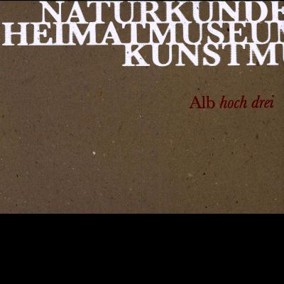"""Das Katalogcover zeigt einen grau-braunen Hintergrund, vor dem in weißen Großbuchstaben geschrieben steht """"Naturkundemuseum, Heimatmuseum, Kunstmuseum"""". Außerdem ist in rot zu lesen """"Alb hoch drei""""."""