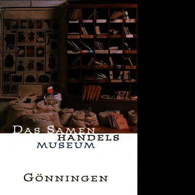 Das Katalogcover zeigt ein Foto von einem Holzregal mit vielen Fächern, die mit Büchern und Briefumschlägen gefüllt sind, gefüllten Säcke sowie einem Plakat im Hintergrund, das verschiedene Pflanzen zeigt.