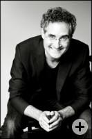 Das in Graustufen gehaltene Foto zeigt den sitzenden Pianisten Matthias Kirschnereit, der einen Anzug trägt und seine Hände im Schoß faltet.