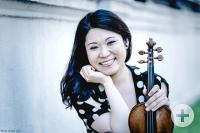 Tianwa Yang lächelt mit ihrer Violine in der Hand in die Kamera.