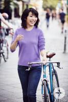 Das Foto zeigt die Pianistin Claire Huangci, die ein Fahrrad schiebt und dabei in die Kamera lächelt.