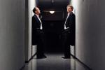 Das Piano-Duo GrauSchumacher steht, an eine Wand lehnend und mit Anzug bekleidet, in einem spärlich beleuchteten Flur.