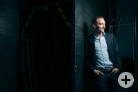 Das Bild zeigt den Dirigenten Moritz Gnann, der mit einem Anzug bekleidet an einer Mauer lehnt und nach rechts blickt.