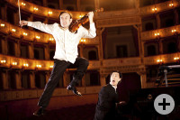 Zwei Musiker in einem Opernsaal: Auf der linken Seite springt ein Musiker mit einer Geige in die Luft, auf der rechten Seite sitzt ein anderer Musiker an einem Flügel und schaut den Kollegen überrascht an.