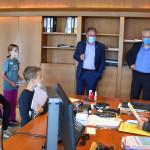 Oberbürgermeister Keck und Verwaltungsbürgermeister Hahn stehen bzw. sitzen gemeinsam mit fünf Kinder um den Schreibtisch im OB-Büro.