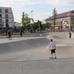 Der Skatepark im Bürgerpark von Bauzaun umgeben, mehrere Skater sind auf der Bahn unterwegs.