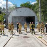Mehrere Feuerwehrleute stehen vor einem rauchenden Bahntunnel bei einer Brandübung.