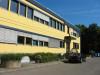Außenansicht eines Bürogebäudes mit hellgelber Fassade. Teilweise wurden an den Fenstern die Jalousien herabgelassen und ein Auto parkt vor dem Gebäude.