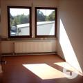 Blick durch die geöffnete Tür in einen kleinen Raum mit zwei Fenstern