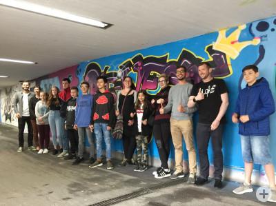 Jugendliche vor einer Graffitiwand