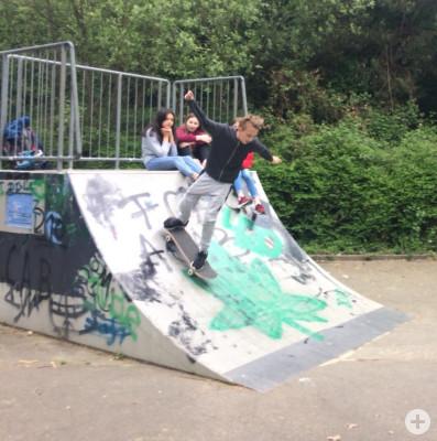 Jugendlicher auf Skateboard fährt von der Rampe