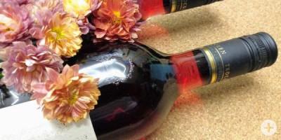 Bild mit zwei Weinflaschen und Blumendeko