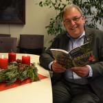 """Oberbürgermeister Thomas Keck sitzt an einem Tisch mit Adventskranz und hält das Buch """"Lebenswerte Geschichten"""" in der Hand"""