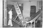 Arbeiter mit Sackkarre in der Cola-Abfüllanlage Betzingen