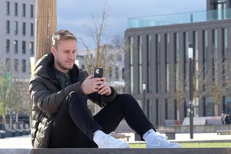 Ein junger Mann sitzt an einen Baum gelehnt im Bürgerparkt und schaut in sein Smartphone