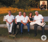 Auf dem Foto sieht man die Mitglieder der Band auf einer Bank