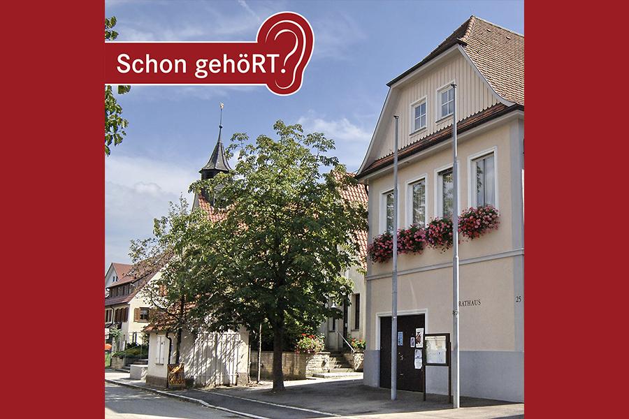 Rathausgebäude in Reicheneck, im Hintergrund ein Baum und eine Kirche