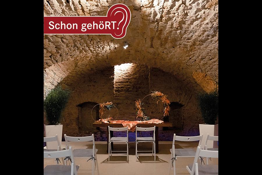 Gewölbekeller mit einem dekorierten Trautisch und Stühlen