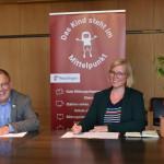 Oberbürgermeister Thomas Keck und Dr. Lea Schüzen sitzen an einem Tisch und unterzeichnen die Zielvereinbarung.
