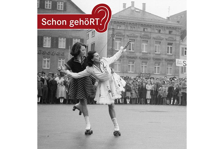 Schwarzweißbild: Zwei rollschuhfahrende Frauen auf dem Reutlinger Marktplatz. Im Hintergrund sind viele Zuschauer zu sehen.