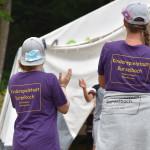 Zwei Frauen im lila T-Shirt mit der Aufschrift Kinderspielstadt Burzelbach auf dem Rücken