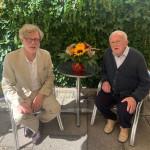 Bürgermeister Alexander Kreher sitzt neben dem 100 jährigen Heinz Parthum und zwischen ihnen steht ein Tisch mit einem Blumenstrauß drauf