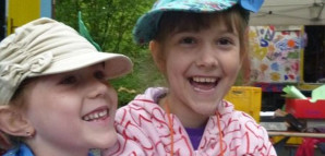Zwei Mädchen mit Kopfbedeckungen lächeln sich an.