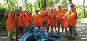 Die Reutlinger Betriebsdienste besuchen den Technischen Bubadienst: Kinder tragen Warnwesten und stehen hinter gefüllten Mülltüten.