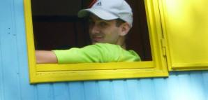 Ein Kinderspielstadt-Betreuer schaut den Betrachter des Bildes aus einem Fenster heraus an