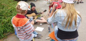 Kinder hören einem jungen Mann beim Gitarrespielen zu