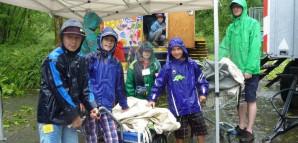 Kinder schützen sich unter einem Zelt vor dem Regen