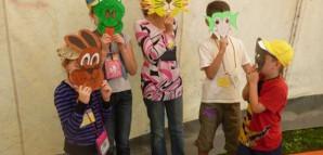 Kinder tragen bunte Tiermasken