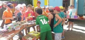 Das Kaufhaus Buba: Kinder sehen sich im Kaufhaus-Zelt die auf einem Tisch ausgebreiteten Waren an.