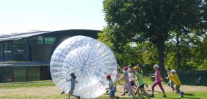 Kinder spielen mit großen durchsichtigen Bubble Balls, in die man hineinschlüpfen kann