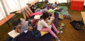 Kinder sitzen auf einer Luftmatratze und lesen Bücher.