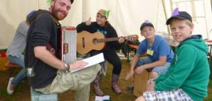 Straßenmusik in Burzelbach: Kinder und Betreuer musizieren mit Gitarre, Akkordeon und Cajon.