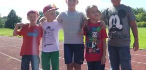 Fünf Kinder unterschiedlicher Größe stehen auf dem Sportplatz in einer Reihe und lächeln in die Kamera.